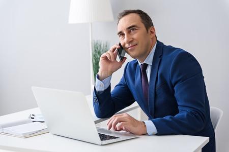 Parlando attraverso il contratto. Sparato dell'uomo adulto di affari che parla sul suo cellulare e che si siede allo scrittorio in ufficio