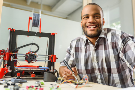 prototyping: Happy male technician is working with 3d printer details. He is holding tester and smiling Stock Photo