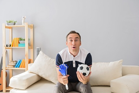 closely: In anticipation of final goal. Adult man watching football match while sitting on white couch at home and closely following game
