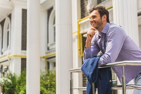 Carefree young man enjoying urban architecture. He is looking forward with admiration and smiling. Guy is standing on balcony and carrying jacket Stock Photo