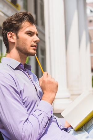 talented: Talented young man is writing poem with inspiration. He is touching pencil to chin pensively. Guy is sitting in city Stock Photo