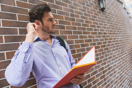 Puzzled male student is thinking with seriousness. He is standing near wall and holding folder