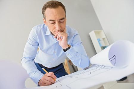 Io so come risolvere questo compito. ritagliata colpo di gravi adulti architetto in piedi vicino al tavolo e guardando il disegno, toccare il viso con la mano