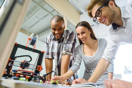 Glückliche junge Ingenieure benutzen 3D-Drucker im Büro . Sie lächeln und lächeln Standard-Bild