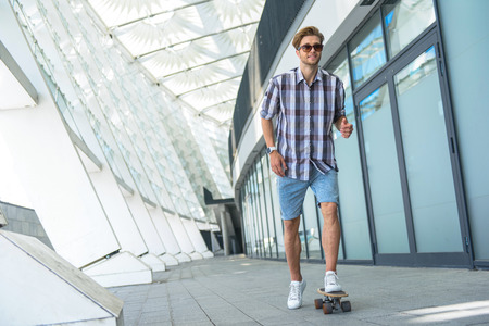 Joyful young man is riding skateboard and smiling