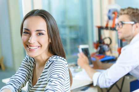 Joyful creative team is resting while 3d printer working. Woman is looking at camera and smiling. Man is holding tablet and sitting at desk on background Stock Photo