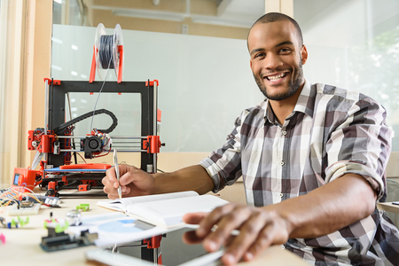 prototyping: This 3d printer is wonderful. Joyful male engineer is doing research in technology lab. He is sitting and making notes. Man is looking at camera and smiling Stock Photo
