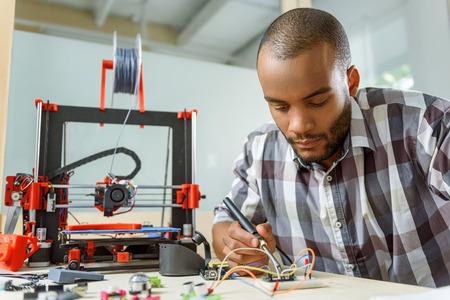 スマートな若い男は、3 d プリンターをエンジニア リングです。彼が座っていると、はんだツールを使用して