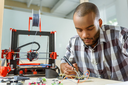 Smart young man is engineering 3d printer. He is sitting and using solder tool