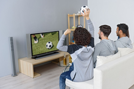 they are watching: Young men and women are watching football match together. They are sitting on couch with anticipation. Girl is raising ball up. Focus on their back Stock Photo