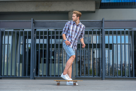 Funky young man is escaping from someone on skateboard. He is looking back with fear
