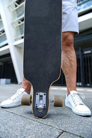 #62647794   Schließen Sie Oben Vom Jungen Mann Der Beine, Der Draußen Nahe  Skateboard Steht