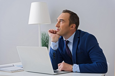 cropped shot: Thinking up new plan of action. Cropped shot of thoughtful-looking adult man sitting in his office near digital tablet Stock Photo