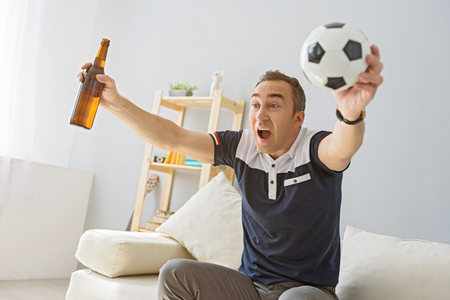 enthusiastically: This is our victory. Handsome man celebrating victory of his team, holding bottle of beer and ball in hands Stock Photo