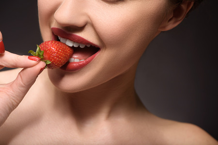 flirty: Flirty girl is biting strawberry with desire. Isolated Stock Photo