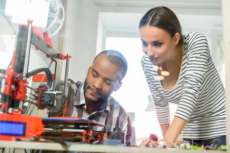 Ingenieros jóvenes alegres están utilizando la impresora 3D en el trabajo. Ellos están buscando a la tecnología con interés Foto de archivo - 62647923
