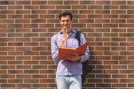 learning by doing: Joyful male student is doing learning subject outdoors. He is standing and leaning on wall. Man is holding textbook and smiling