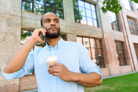 seriousness: Confident African man is talking on smartphone with seriousness. He is standing near building and drinking coffee