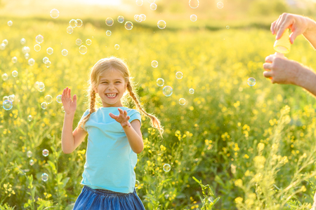 street shot: Everyone loving bubbles. Shot of cute girl trying to touch bubbles floating in air around her outdoors and smiling Stock Photo