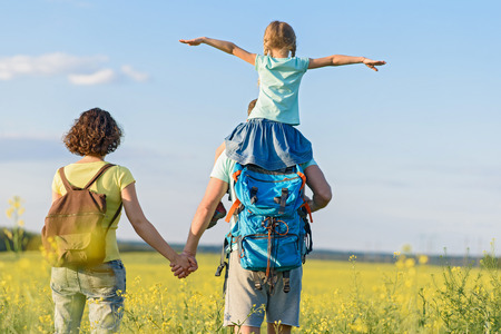 This is so much fun with dad. Little girl with pigtails sitting on father shoulders while they standing in field with her mother Stock Photo