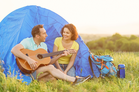serenading: Serenading outdoors. Shot of adult man playing guitar for his girlfriend and sitting near tent