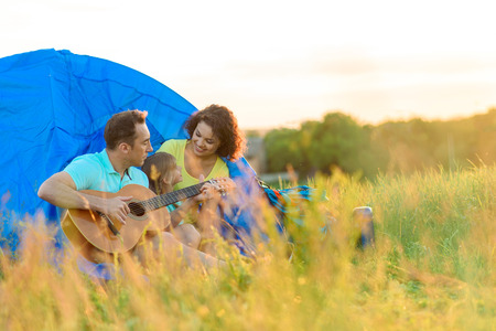 making music: Making music in outdoors. Cute young family spenting their holidays outside on picnic with guitar and sitting near blue tent