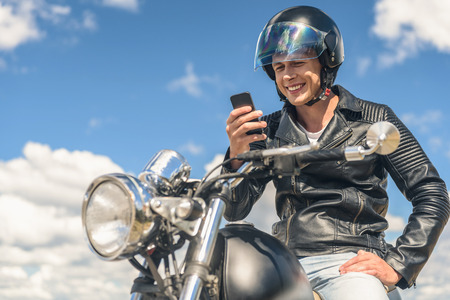 hands connected: Always connected. Close up photo of young guy wearing helmet, holding in hands smartphone, looking on it and smiling Stock Photo
