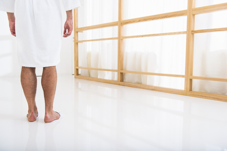 common room: Close up of male legs standing on white flooring near window in restroom. Man is wearing bathrobe. Focus on his back
