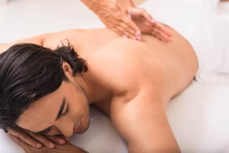 back sprains: closeup view of enjoying face of a man having massage treatment with female hands on his back