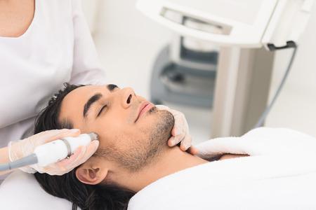 Entspannter junger Mann wird immer elektrische Gesichtsmassage von Kosmetikerin. Er liegt mit geschlossenen Augen Standard-Bild - 62932305