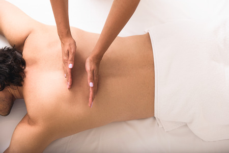 back sprains: overhead view of a man having massage treatment on a spa table