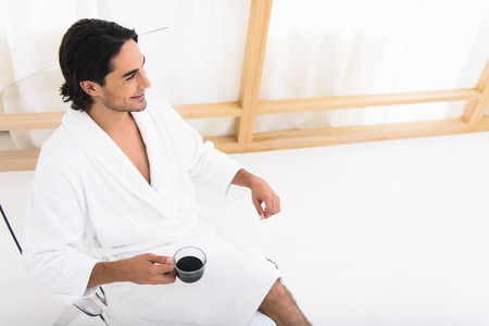 Joyful young man is enjoying his vacation. He is sitting on chair in bathrobe and holding cup of coffee. Man is looking aside and smiling Stock Photo