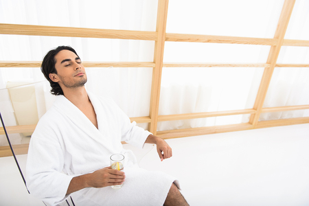 Young man is relaxing with fresh beverage at spa. He is sitting in bathrobe. His eyes are closed with enjoyment