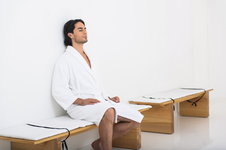 common room: Relaxed young man is enjoying solitude in restroom at wellness center. He is sitting on bench in bathrobe with relaxation