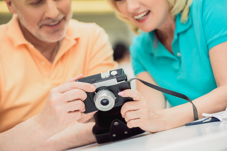 Mature man and woman are looking at photos on camera with interest. They are sitting at table and laughing