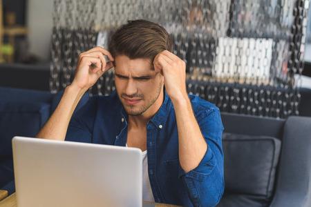 混乱とノート パソコンの前に座っている男を見て、不可能です。