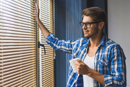guy holding cup of coffee and smiling while looking in the window Reklamní fotografie