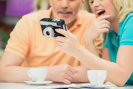 they are watching: Senior married couple is watching photos on camera. They are sitting at table in cafeteria and smiling Stock Photo