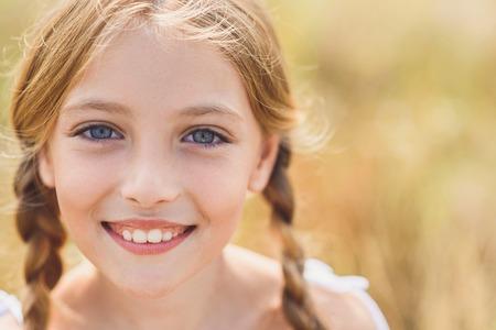 Portret van gelukkig meisje camera kijken met onschuld en glimlachen. Ze staat in de natuur Stockfoto