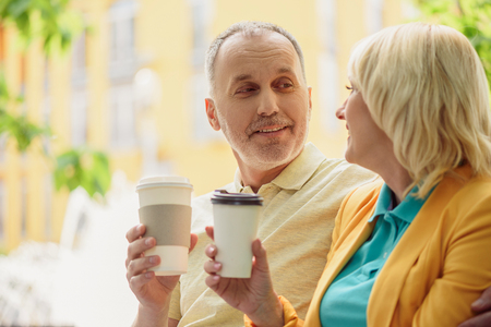 Senior married couple is drinking coffee outdoors. Man is embracing woman and smiling