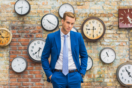 qualified worker: Shot of stylish businessman posing for camera with his hands in pockets against of brick wall with clocks Stock Photo