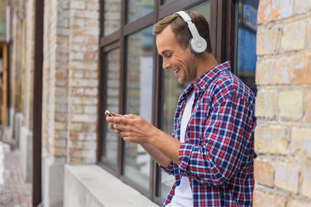 Starting day at positive. Handsome man sitting outside of building and listening to music on headphones, using smartphone