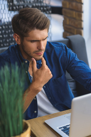 Je pense, l'homme assis devant un ordinateur portable avec le regard philosophique Banque d'images - 63525132
