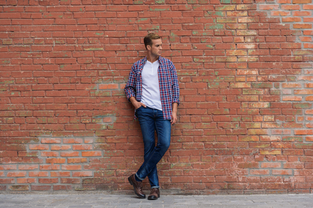 Casual city style. Full growth photo of handsome man leaning against brick wall in urban setting Stock Photo