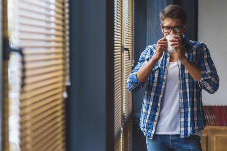 jalousie: satisfied worker drinking tea in front of jalousie