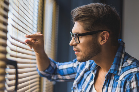 secretly: half face of curious guy in glasses spying thru jalousie Stock Photo