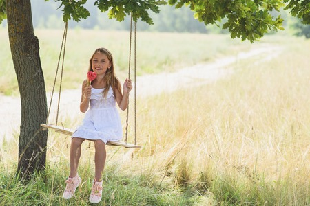 Pretty girl is eating lollipop with enjoyment. She is sitting on swing in meadow. Kid is smiling Stock Photo