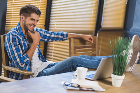 feet up: happy businessman laughing with his feet up on desk Stock Photo