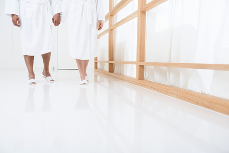 wearing slippers: Cropped shot of couple walking together and holding hands in spa salon, wearing white terry bathrobes and slippers Stock Photo
