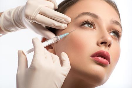 poblíž: Serin mladá žena začíná obličejové injekce botoxu. Kosmetička ruce v rukavicích drží injekční stříkačky v blízkosti obličeje Reklamní fotografie